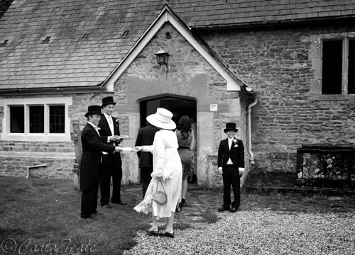 Black and white documentary picture of wedding guests arriving